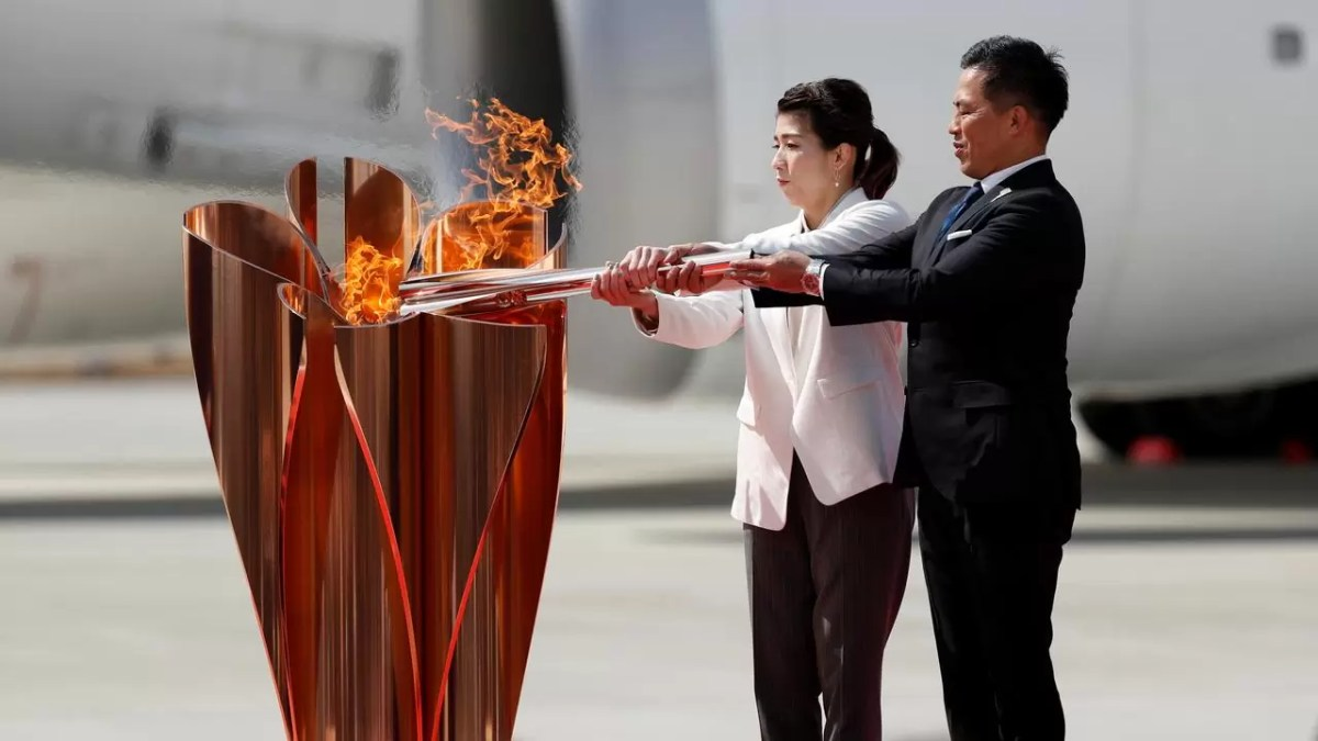 الرياضيان اليابانيان ساوري يوشيدا وتاداهيرو نامارو يحملان الشعلة الأولمبياد