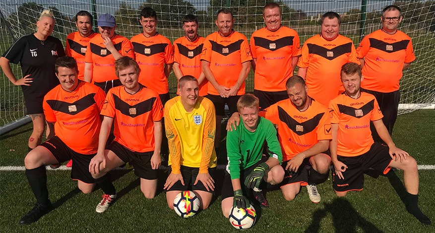 Swale Tigers team pose in their new orange football kit.