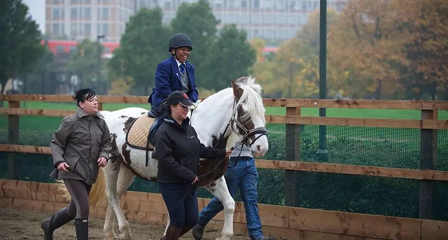 Child having a horse riding lesson at Vauxhall City farm.