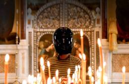 Boy standing in church with racing helmet on