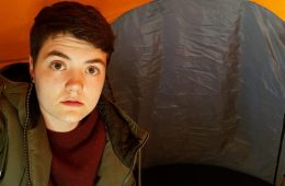Someone sits inside a tent, looking into the camera