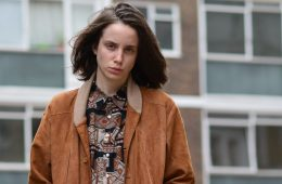 A person wit long hair and feminine features stands outside with a brown jacket, looking into the camera