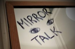 MIRROR TALK is written on a mirror in black marker pen, with a pair of eyes drawn on too