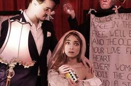 Woman in wedding dress holding a mini caravan, groom holding lamp, man standing above holding a crystal ball and a book of freud.