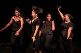 Four Black women are laughing, dancing, and moving onstage, all wearing black and against a black background.