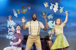 3 performers hold a stick man puppet and paper fish, may be an under water scene
