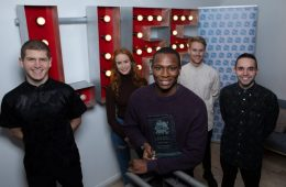The Luke Westlake Scholarship finalists gather in front of a neon sign, with Ayomide Adegun at the front, holding his award.