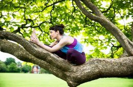 A woman sits in a tree, stretching her leg out, wearing a spandex yoga outfit.