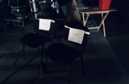 "A photo from the set of a Kenco advert. Two black chairs are on set with the names ""Emma"" and ""Emily"" taped onto them."