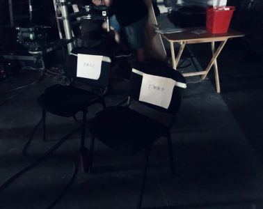 """A photo from the set of a Kenco advert. Two black chairs are on set with the names """"Emma"""" and """"Emily"""" taped onto them."""