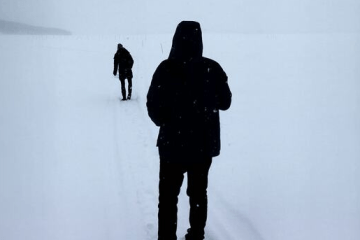 Snowy background with two figure. Both have their backs to us and seem like silhouettes. One is in front making tracks, the other is following