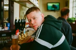 Samuel Bailey wear a dark green hoodie with white detailing. He leans over a pub bar, holding a pint of beer, and looks towards the camera.
