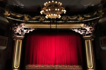 A picture of a theatre's stage. It has red curtains, golden proscenium arches, and a chandelier.