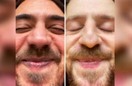 Two male faces beside eachother on Zoom. Smiling with eyes closed, really close up to the camera.