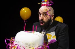 A man with a surprised expression is holding a birthday cake and wearing a brightly coloured party hat.