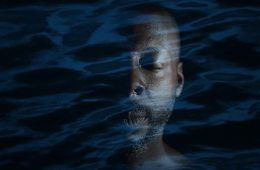 A close up of a man. Overlaid over his image is an effect that makes it look like he's drowning in a dark sea.