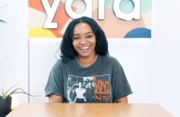 A picture of Amahra Spence sitting at a table, laughing, with the word 'yara' behind her.