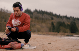 A young person on a beach, using a phone.