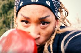 A close-up of a women wearing a boxing glove, gearing up for a punch.