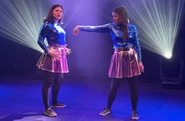 Two women dressed in shiny outfits are on a stage. There is strobe lighting behind them.