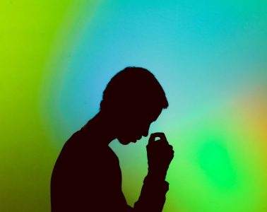 A silhouette of a man looks mournfully down and a cascade of blues, acid greens and yellows form his background