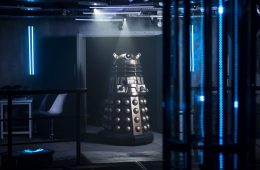 A dark room with blue neon lights. A robot called Dalek in the room.