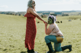 Woman and a fairy with a painted green face who are in a field