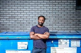 A man stands in front of large recycling collection bins. He has his arms crossed and is looking directly at the camera with a neutral expression.