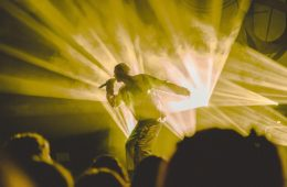A man stands on stage with a microphone. He is lit in yellow strobe lights.