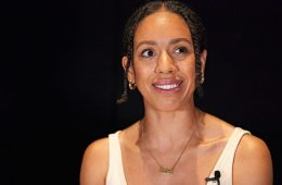 An actress smiling, standing against a black backdrop.
