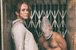 In a confined space are a woman looking directly in the camera, and a bound man with a plastic bag over his head.