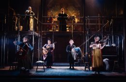 A stage view of the entire cast playing various instruments.