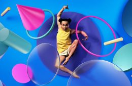 A person is in an acrobatic pose, surrounded by brightly coloured shapes.