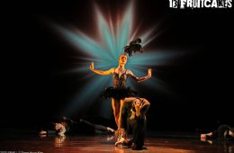 A ballerina poses in the centre of a stage, whilst other dancers pose variously around them.