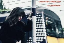 A woman in. black coat walking outside, a commuter train behind her.