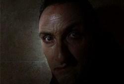 A man's face in shadow, the man wears a dark coat