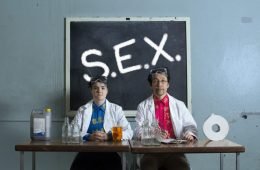 Iriguchi (the writer) stands on the right in a lab coat and goggles, next to his assistant who is dressed similarly. Behind them on a blackboard spell the letters S.E.X.
