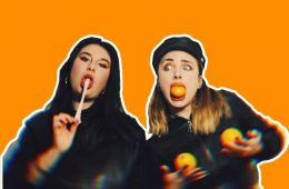 Two women on a bright orange background, the one on the left chewing gum and the other holding oranges