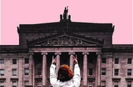A girl with red hair puts two middle fingers up to a constitutional building