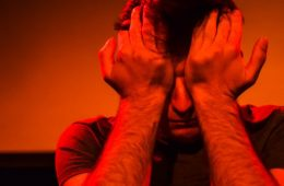A person holds their head in their hands, with a bright red light shining on them.