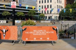 An orange barrier with the words 'Welcome to the great open air theatre Manchester' sits in a square in the city