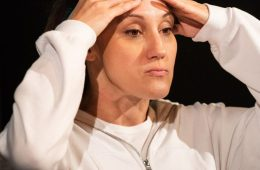 An actor in a white hoodie stands with her hands on her head