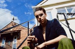 A man smoking outside a house
