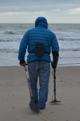 man using Metal Detector on beach