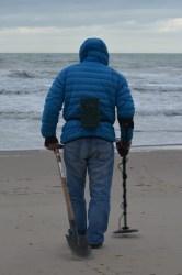 man using Metal Detector on beach