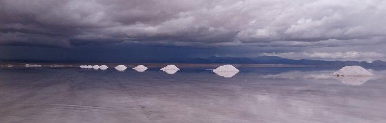 De zouthoopjes steken mooi af tegen de donkere regen lucht. Salar de Uyuni