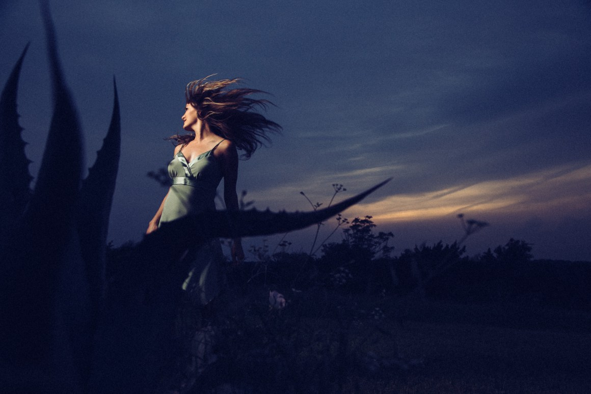 Workshop Model. Leah framed against a Terradorna sunset with a cactus in the foreground. Energetic and a wee bit mysterious
