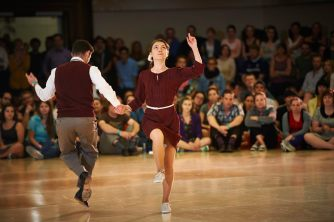 People swing dancing in a dance competition. Photo by me.