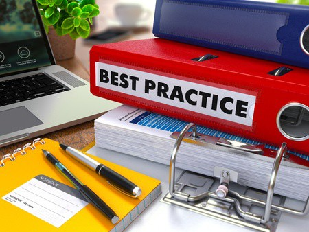 Red Ring Binder with Inscription Best Practice on Background of Working Table with Office Supplies, Laptop, Reports.