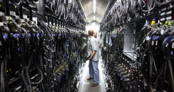 Picture of two guys standing in an aisle between rows and rows of complex computer servers in a massive data center